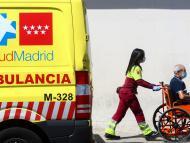 Una trabajadora de la Sanidad madrileña acompaña a un hombre en silla de ruedas al Hospital 12 de Octubre