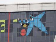 Unos trabajadores sustituyen el logo de Bankia por el de CaixaBank en los edificios Puerta de Europa de Madrid