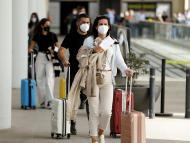 Turistas con maletas salen del aeropuerto.