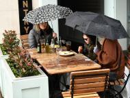 Amigas en una terraza mientras llueve