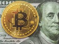 Un bitcoin sobre un billete de 100 dólares.