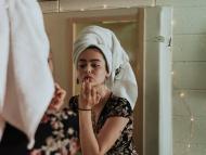 chica en el baño cuidándose la piel, maquillándose