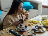 Chica comiendo comida basura, refrescos, atracón