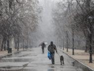 Un hombre camina bajo la lluvia en el Retiro
