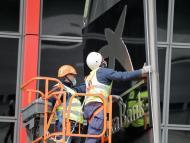 Unos operarios colocan el logo de CaixaBank en las torres KIO.