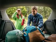 Pareja metiendo las maletas en el coche
