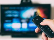 Una persona viendo la tele con el mando en la mano