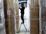 Una trabajadora con mascarilla revisa cajas de ataúdes en un almacén logístico