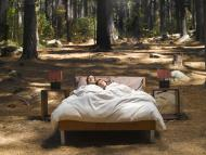2 personas duermen en una cama en medio del campo.