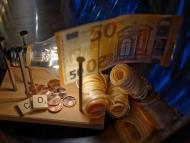 Un billete, varias monedas y un bombilla.