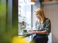 Una mujer joven trabaja con su ordenador portátil en la cafetería de un coworking