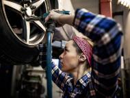 Una mujer reparando unos neumáticos