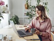 Una mujer repasando documentos en el ordenador