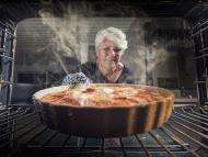 Una mujer saca una tarta de manzana del horno.