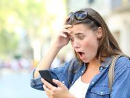 Una mujer se sorprende al mirar el móvil.