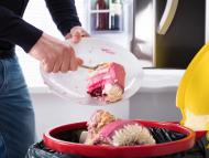 Tirando comida al cubo de basura