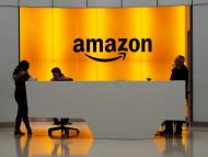 Amazon office front-desk staff stand in front of an orange sign with the Amazon smile logo