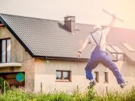 Un arquitecto salta delante de una casa recién edificada.