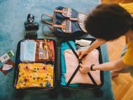 Una chica hace la maleta para irse de vacaciones en verano.