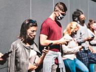 Un grupo de jóvenes mira su teléfono móvil en la calle durante la pandemia