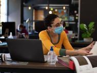 Mujer diseñadora trabajando en una cafetería con mascarilla puesta.