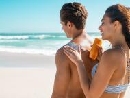 Una mujer le pone crema solar a un hombre en la playa