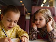 Un niño y una niña viajan en tren.