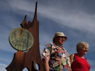 Una pareja delante de un monumento a la peseta