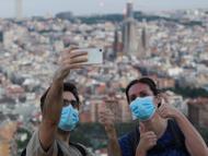 Una pareja de turistas con mascarillas se hace un selfie en Barcelona durante la pandemia de coronavirus