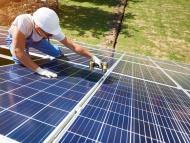 Un trabajador instala una placa solar.