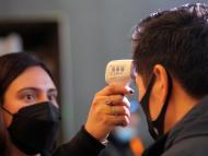 Una trabajadora controla la temperatura de un asistente a un evento en Nueva York