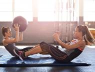two workout partners facing each other in a sit-up position on gym mats, tossing a medicine ball