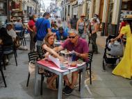 Gente comiendo en una terraza de un bar.