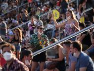 Gente en un concierto al aire libre con y sin mascarillas.