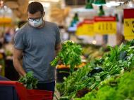 Un hombre compra verduras en el supermercado.