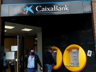 Un hombre saca dinero en un cajero de CaixaBank
