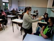 Una profesora toma la temperatura a un alumno en clase
