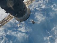 soyuz spacecraft approaches zarya module cylinder with solar panels above blue earth oceans