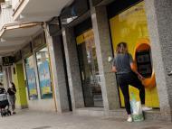 Clientes sacando dinero en un cajero de CaixaBank