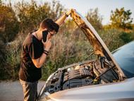 Un conductor revisa su coche estropeado