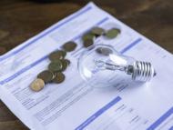 Una factura de la luz con una bombilla y unas monedas encima.