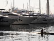 Un hombre cruza en canoa la marina de yates del puerto de Palma de Mallorca