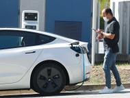 Un hombre mira su móvil mientras carga un coche eléctrico en Sant Cugat del Valles