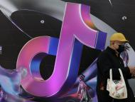 Un hombre pasando frente a un logo de TikTok