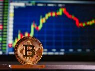 Una moneda de bitcoin delante de un gráfico.