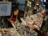 Una mujer paga en una pescadería con una tarjeta de débito.