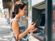 Una mujer sacando dinero con el teléfono móvil