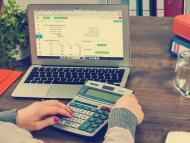 Una persona con una calculadora y un ordenador.