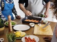 personas cocinando salmón