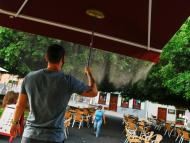 Un chico abre la terraza de un bar.